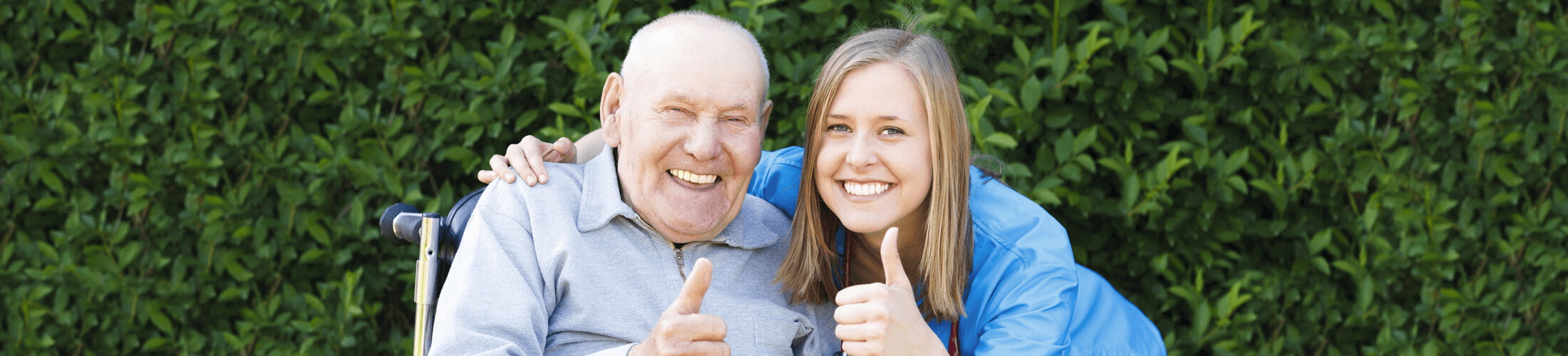 An elderly man and a young lady giving a thumbs up to the camera