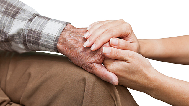 An elderly mans hand being held comfortingly