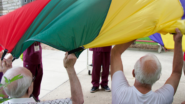 A group of seniors and care staff waving a parachute