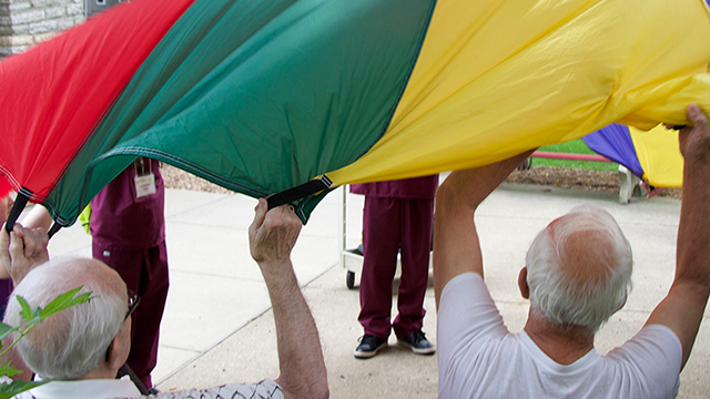 A group of nursing home employees and residents engage in a group activity holding a parachute